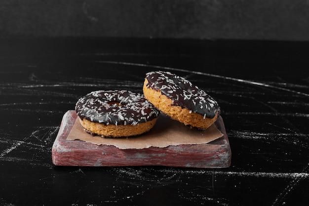 Donuts de chocolate em uma placa de madeira