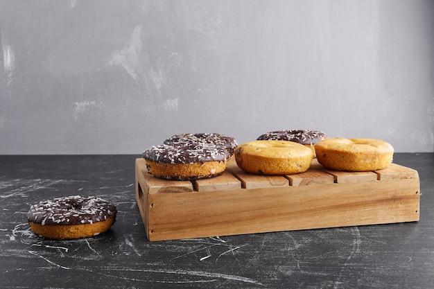 Donuts de chocolate em uma superfície preta em uma bandeja de madeira.