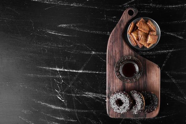 Donuts de chocolate em uma travessa de madeira com biscoitos ao redor.