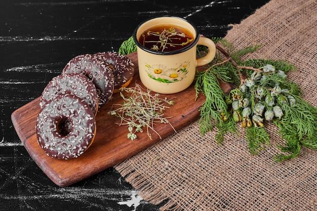 Donuts de chocolate em uma travessa de madeira com chá de ervas.