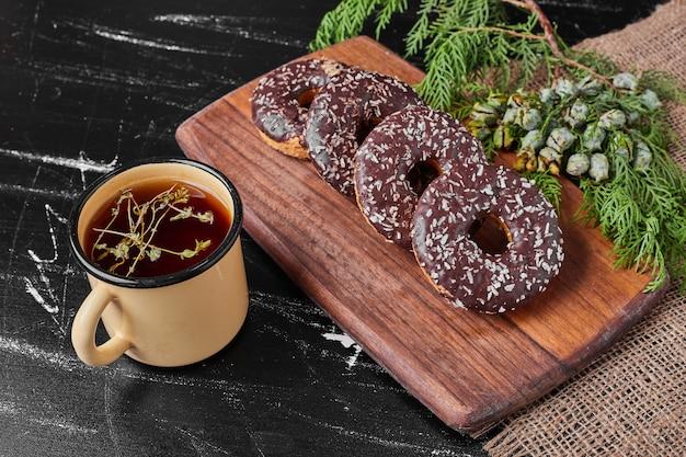 Donuts de chocolate em uma travessa de madeira com chá.