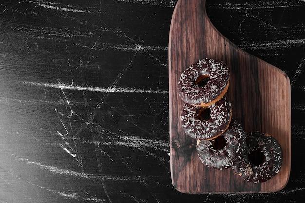 Donuts de chocolate em uma travessa de madeira.