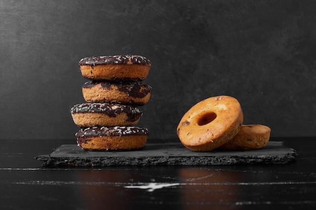 Donuts de chocolate em uma travessa de pedra.