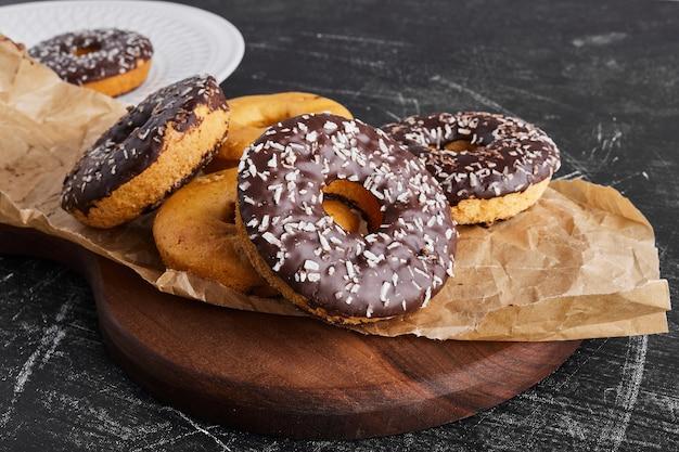 Donuts de chocolate em uma travessa rústica.