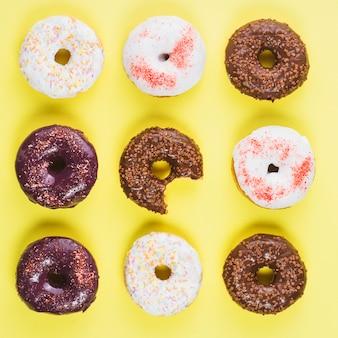 Donuts de chocolate marrom e branco com polvilha e falta de mordida