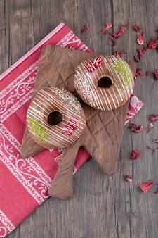 Donuts de chocolate na placa de madeira com pétalas de rosa secas.