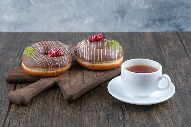 Donuts de chocolate na placa de madeira com uma xícara de chá preto.