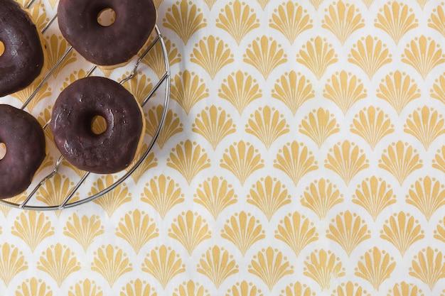 Donuts de chocolates em rack de metal sobre o papel de parede dourado