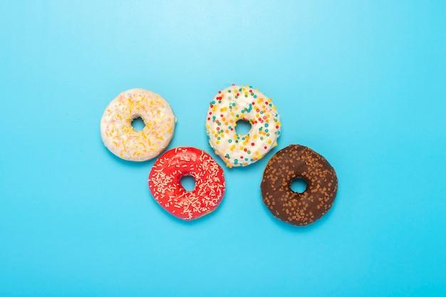 Donuts de diferentes tipos em um espaço azul. conceito de doces, padaria ,. bandeira. camada plana, vista superior.