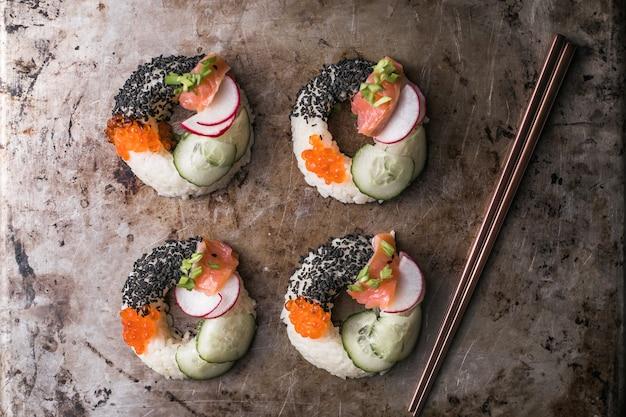 Donuts de sushi com salmão, pepino e rabanete na vista superior de metal