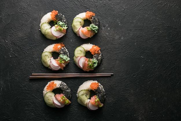 Donuts de sushi com salmão, pepino e rabanete na vista superior escura