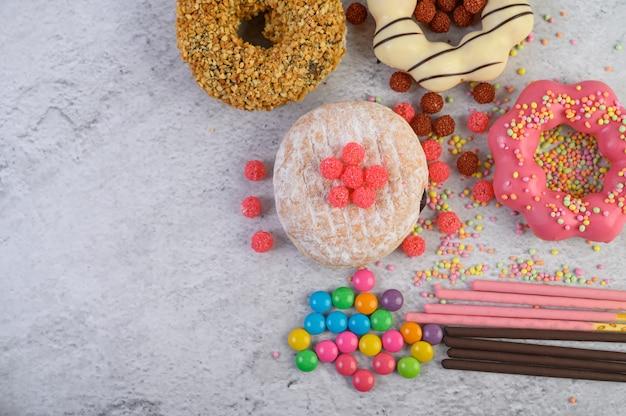 Donuts decorados glacê e granulado na vista superior de superfície branca