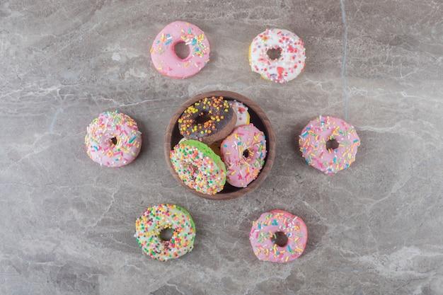 Donuts dentro e ao redor de uma pequena tigela na superfície de mármore