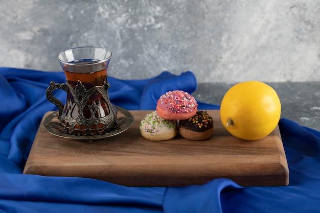 Donuts doces coloridos com uma xícara de chá.