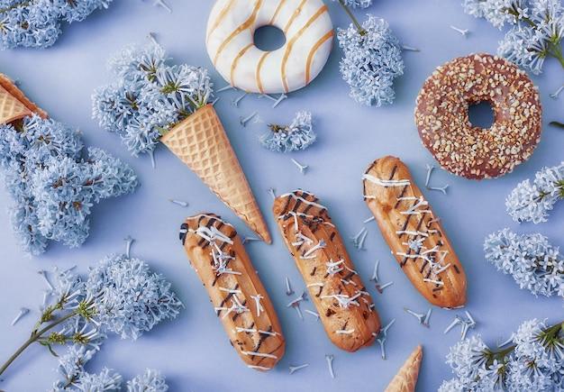 Donuts e bolos de creme com flores lilás em papel azul