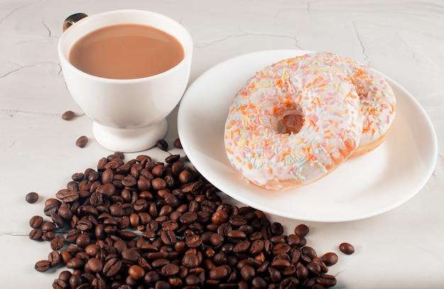 Donuts e café com leite natural em uma superfície clara. lixo
