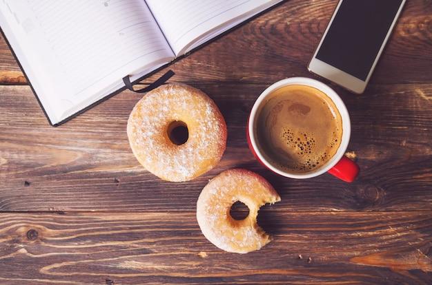 Donuts e café deitado na superfície de madeira rústica com o bloco de notas aberto e o telefone celular. vista do topo. imagens retrô em tons.