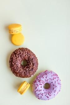 Donuts e macarons vitrificados. sobremesa doce isolada no fundo verde suave.