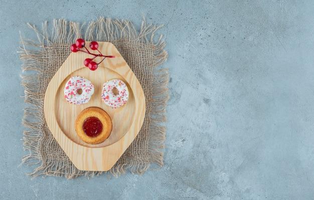 Donuts e um bolo cheio de geleia em uma bandeja de madeira com fundo de mármore. foto de alta qualidade