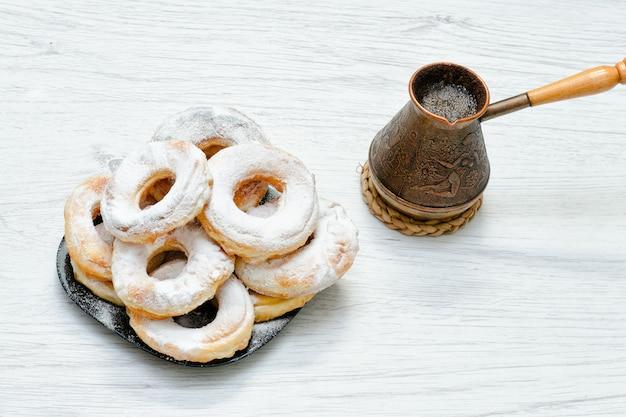 Donuts em açúcar de confeiteiro e cafeteira em um fundo de madeira