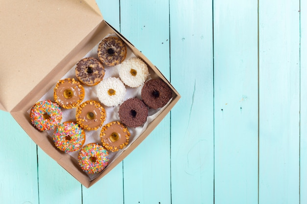 Donuts em caixa na mesa de madeira. vista do topo
