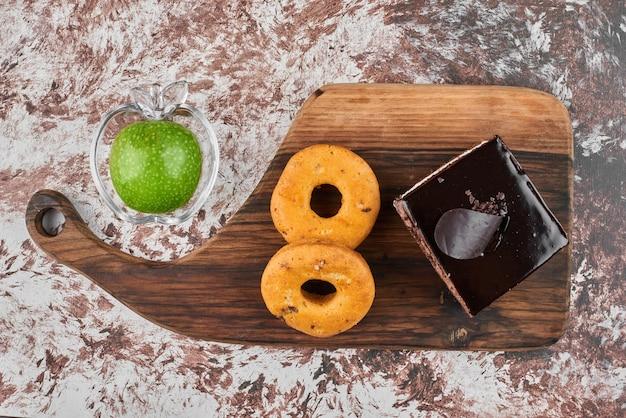 Donuts em uma placa de madeira com uma fatia de cheesecake de chocolate.