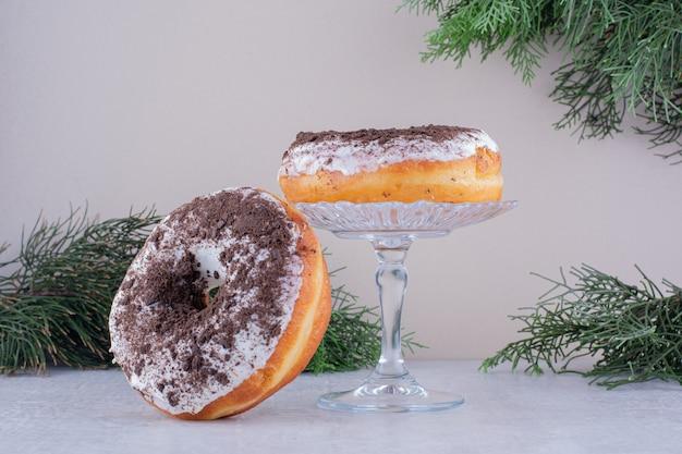 Donuts encostado a um suporte de vidro em fundo branco.