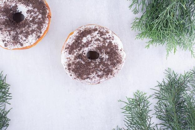 Donuts expostos entre folhas de pinheiro em uma superfície branca