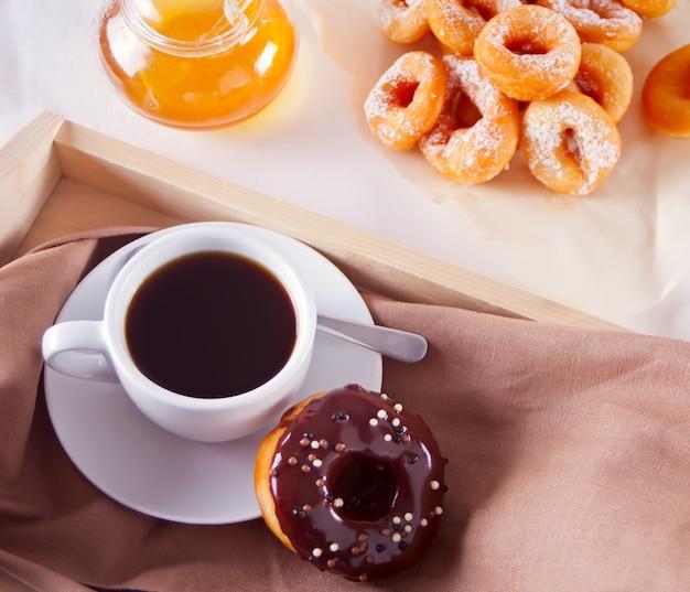 Donuts frescos com café na mesa de madeira