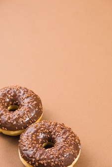 Donuts frescos com cobertura de chocolate escuro e polvilha