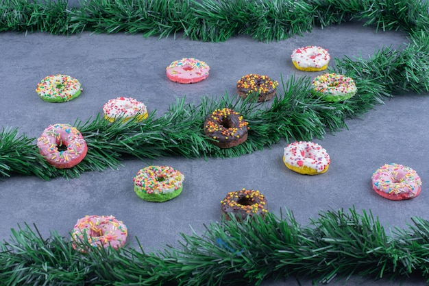 Donuts frescos e doces coloridos em uma superfície cinza