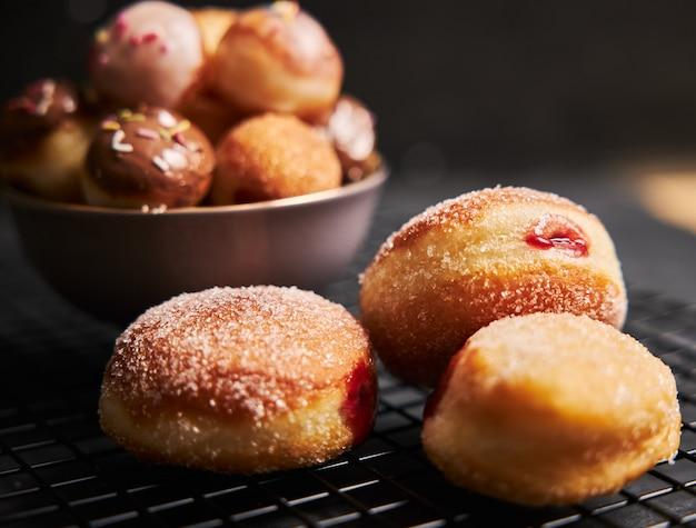 Donuts fritos com açúcar e creme em uma mesa preta