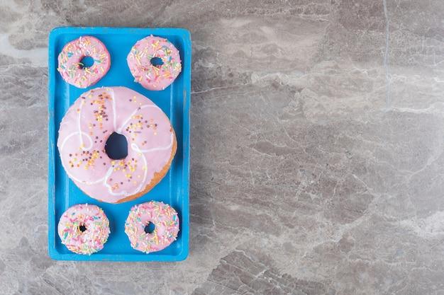 Donuts grandes e pequenos dispostos em uma bandeja azul na superfície de mármore