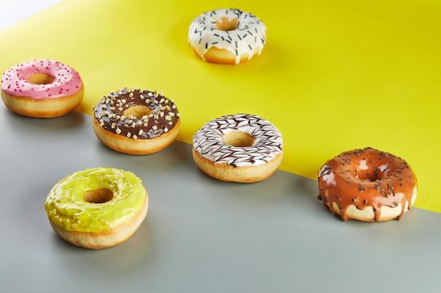 Donuts multicoloridos com esmalte e granulado em um fundo cinza-amarelado