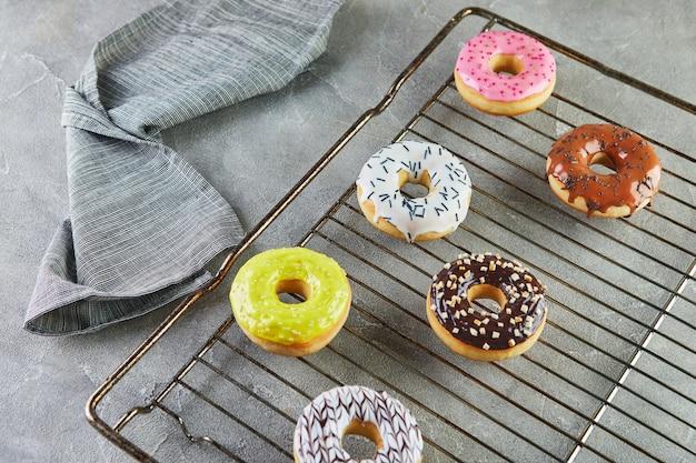 Donuts multicoloridos com esmalte e granulado em um suporte de metal do forno e um guardanapo cinza.