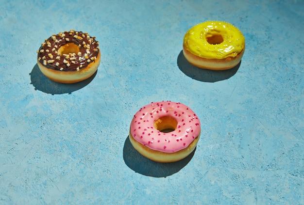 Donuts multicoloridos com glacê e granulado sobre fundo azul.