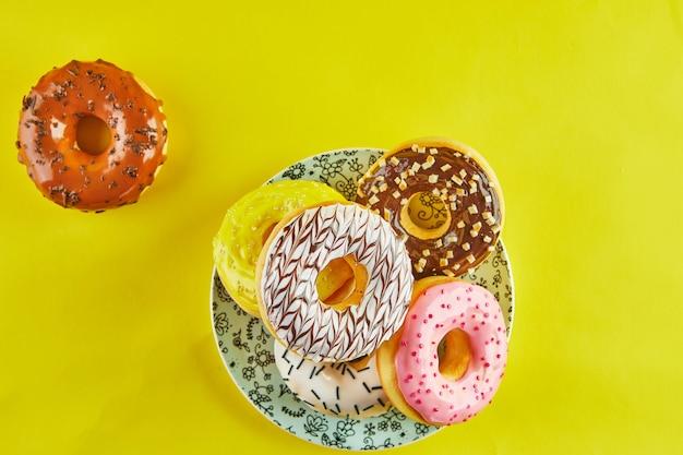 Donuts multicoloridos com glacê e salpicos em uma placa azul sobre um fundo amarelo. postura plana