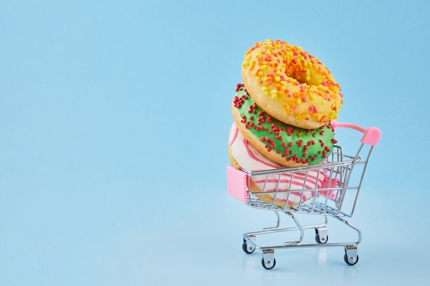 Donuts no carrinho de compras pequeno. carrinho de compras e donut vitrificado em fundo azul pastel.