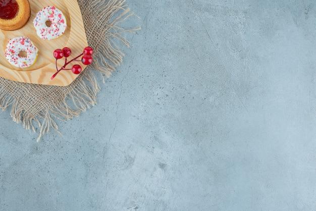 Donuts pequenos e um bolo recheado de geleia em uma bandeja de madeira com fundo de mármore. foto de alta qualidade