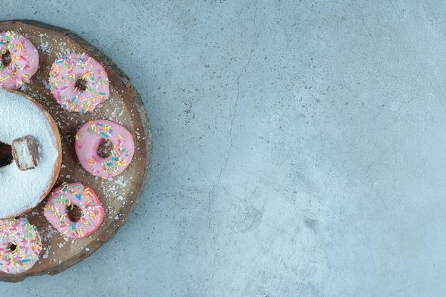 Donuts pequenos em torno de um donut grande em uma placa de madeira no mármore.