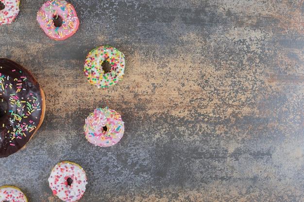 Donuts pequenos em torno de um donut grande em uma superfície de madeira
