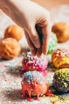 Donuts polvilhado por uma mulher com açúcar granulado.
