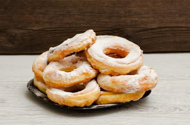 Donuts polvilhados com açúcar de confeiteiro, fundo escuro de madeira. close-up, vista lateral