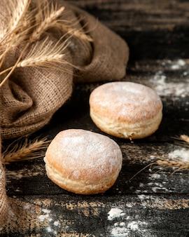 Donuts recheados com creme de manteiga e açúcar em pó na mesa