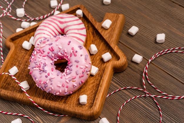 Donuts repousam sobre uma tábua em forma de casa em um fundo de madeira