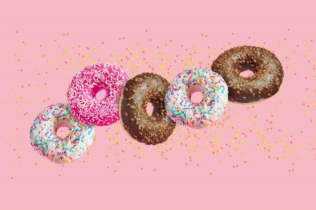 Donuts vitrificados em movimento caindo no rosa com granulado colorido