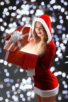 Donzela de neve em terno vermelho, segurando um presente para o ano novo