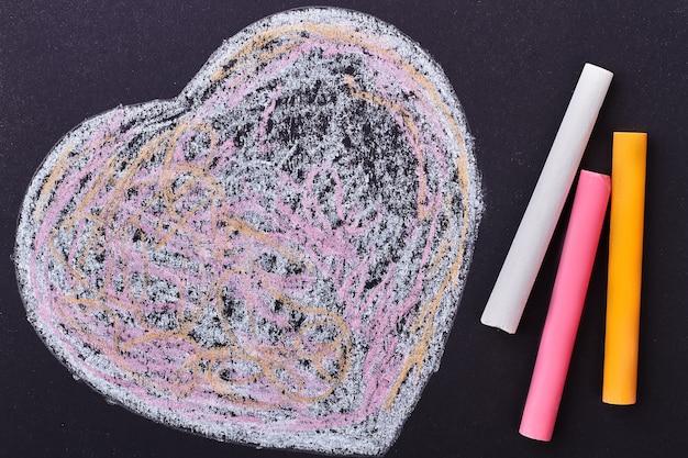 Doodle coração em fundo preto. varas e coração de giz colorido. surpresa simples, mas criativa.