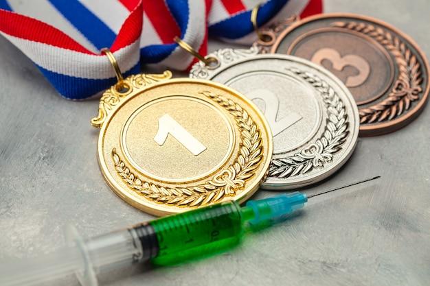 Doping para atletas. ouro, medalha de prata e bronze e seringa de doping em superfície cinza.