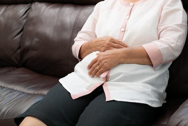 Dor abdominal, dor de estômago, mulher idosa que sofre
